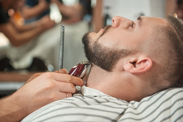 Close up portrait of a handsome young bearded man getting his beard trimmed by a professional barber. Free Photo