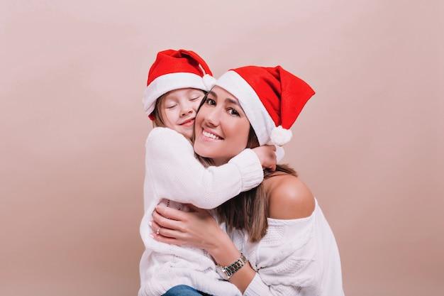 Close up ritratto di famiglia felice che indossa cappelli di natale e maglioni bianchi Foto Gratuite