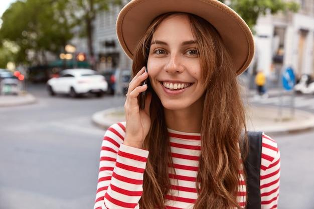 Close up ritratto di modello femminile felice chiama operatore di servizio, passeggia in centro, utilizza la connessione in roaming, gode di viaggio all'estero, ha i capelli lunghi Foto Gratuite