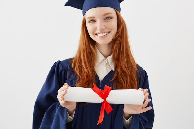 Close up portrait of happy foxy woman graduate in cap smiling holding diploma. young redhead woman student future lawyer or engineer. Free Photo