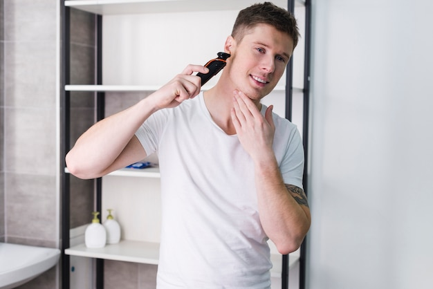 Close-up portrait of happy man looking on camera and shaving his face with electric razor Free Photo
