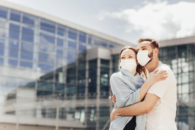 Close up portrait of happy man and woman in protective masks after coronavirus quarantine. young couple near airport, opening air travel, travel concept Premium Photo