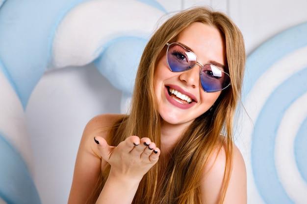 Chiuda sul ritratto di giovane donna felice che posa nello studio vicino a caramelle enormi, capelli lunghi e sorriso di bellezza, indossando occhiali da sole e orologi dal cuore, stile pop. Foto Gratuite