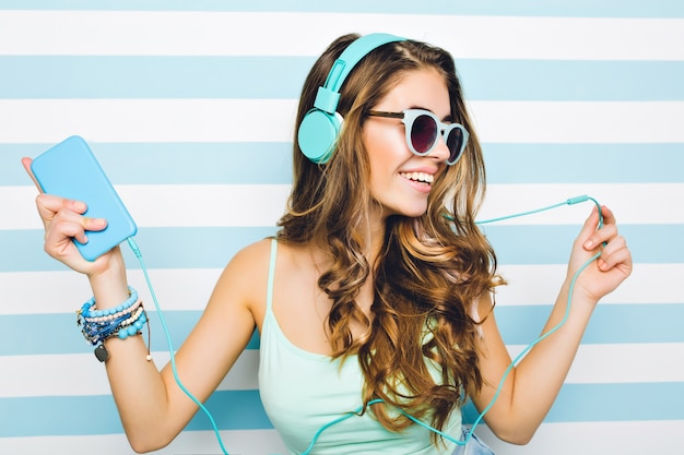 Close-up portrait of joyful girl enjoying music in big headphones, holding mobile phone in hand. attractive young woman wearing black sunglasses and trendy accessories chilling on striped wall. Free Photo