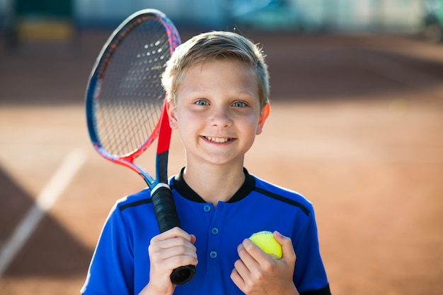 Close-up portrait of kid on the tennis field Free Photo