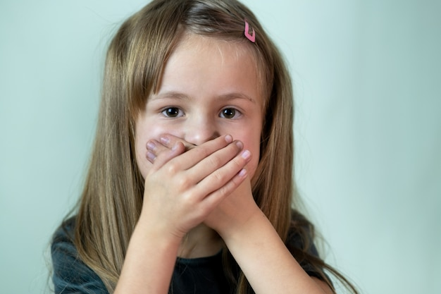 Close-up portrait of little child girl with long hair covering her mouth with hands. Premium Photo