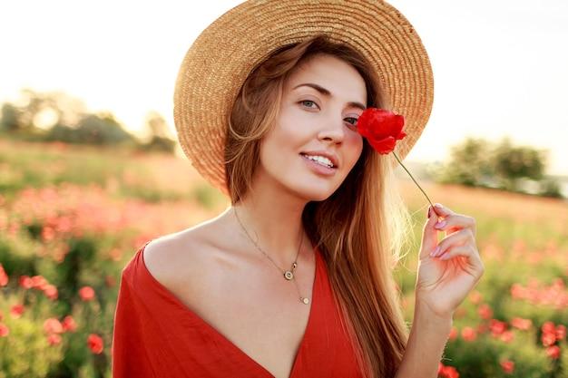 Close up ritratto di bella giovane donna romantica con il fiore di papavero in mano in posa sul fondo del campo. indossare un cappello di paglia. colori tenui. Foto Gratuite