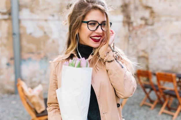 Ritratto del primo piano di bella giovane donna alla data nel caffè all'aperto che tiene bei fiori. affascinante ragazza con bouquet di tulipani attende un amico nel ristorante guardandosi intorno attraverso gli occhiali Foto Gratuite