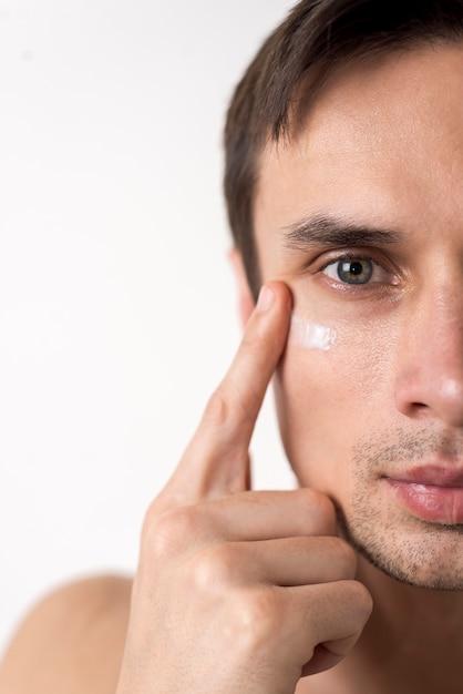 Portrait of smiling mature man applying shaving cream on face against white background high