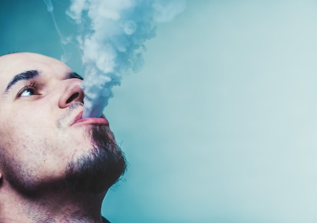 Close up portrait of a man vaping. Premium Photo