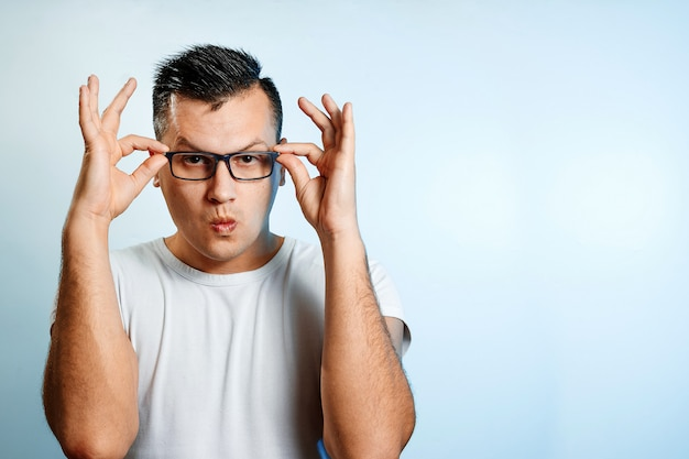 A close-up portrait of a man who straightens his glasses with his hands. Premium Photo