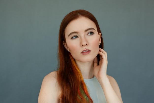 머리에 색깔 된 가닥과 사려 깊은 심각한 모습, 입 벌리고있는 녹색 눈을 가진 아름 다운 빨간 머리 여성 모델의 초상화를 닫습니다. 파란 벽에 포즈를 취하는 예쁜 생강 소녀 무료 사진