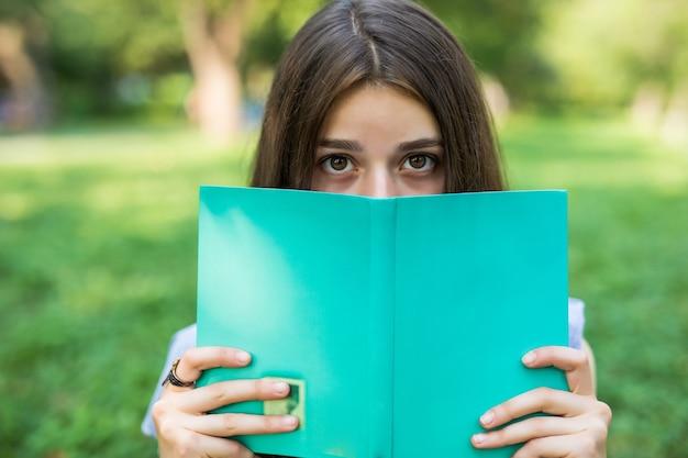 公園で本を持つ美しい若い女性のクローズアップの肖像画 無料写真