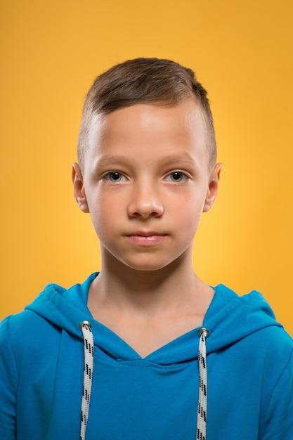 Крупным планом портрет мальчика над желтой стеной Premium Фотографии