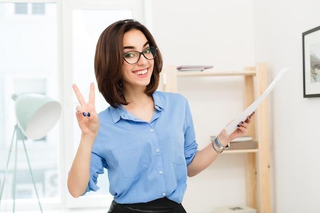 Крупным планом портрет брюнетки в голубой рубашке и черной юбке, стоящей в офисе. она держит в руке бумагу. она очень счастлива улыбается в камеру. Бесплатные Фотографии