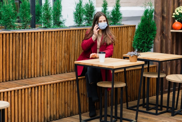 Крупным планом портрет кавказской женщины в медицинской маске, стоящей на улице на фоне кафе Premium Фотографии