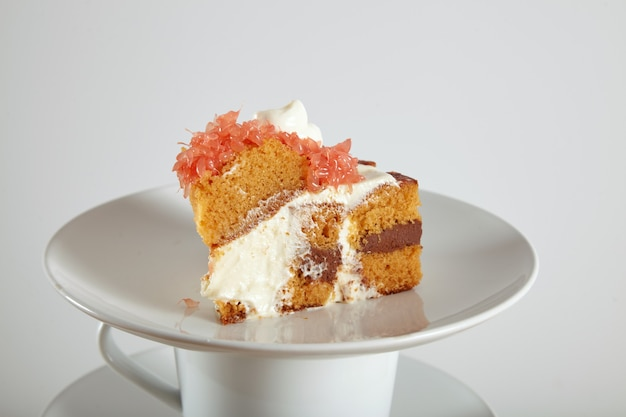 Крупным планом портрет вкусного бисквитного торта с шоколадной начинкой, сливками и грейпфрутом на блюдцах и чашках Бесплатные Фотографии
