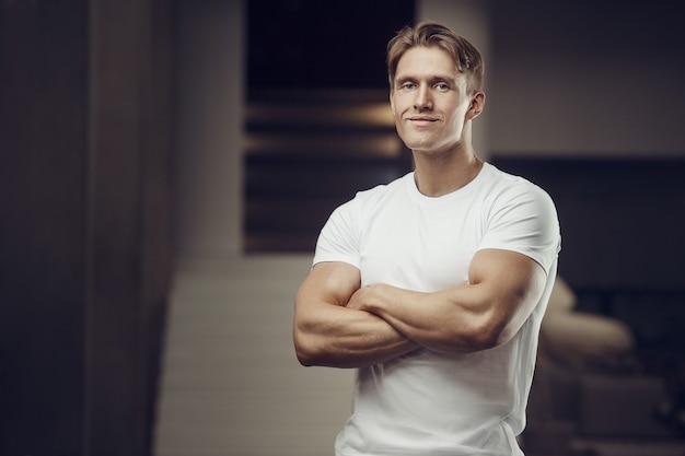 Крупным планом портрет красивого фитнес-мужчины в белой рубашке в тренажерном зале Premium Фотографии