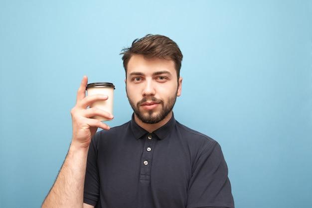 Крупным планом портрет человека с бородой, стоящего на синем с бумажным стаканчиком кофе в руках Premium Фотографии