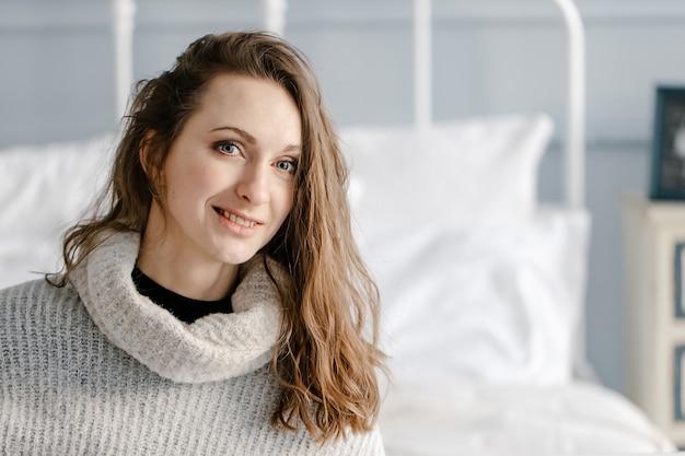 Макро портрет довольно улыбающейся молодой женщины в уютном свитере расслабиться в спальне дома Premium Фотографии