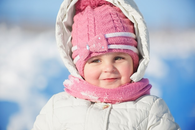 Крупным планом портрет очаровательны девочки в теплой зимней одежде позирует против снега Бесплатные Фотографии