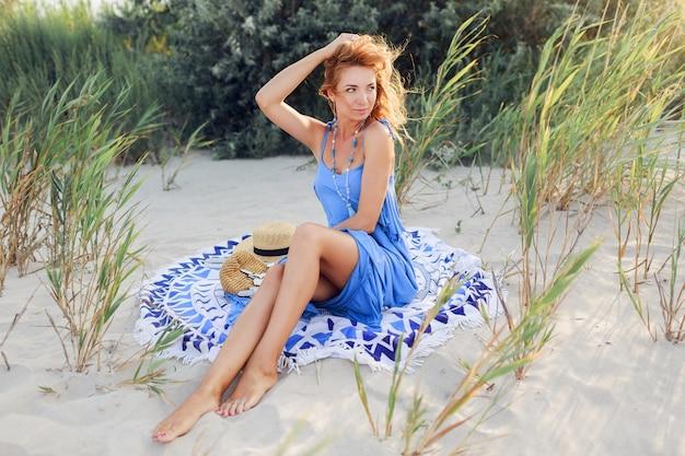 タオルの上の春の太陽が降り注ぐビーチでリラックスした青いドレスの素晴らしい笑顔赤毛の女性の肖像画を閉じます。麦わら帽子、スタイリッシュなブレスレット、ネックレス。 無料写真