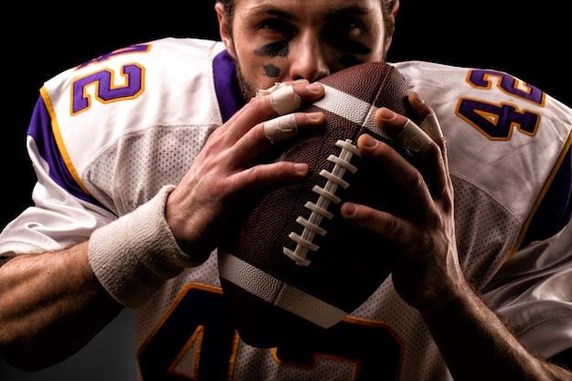 ボールを優しくキスするアメリカンフットボール選手の肖像画を間近します。 Premium写真