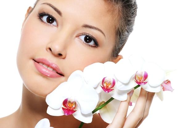 그녀의 얼굴 근처 꽃과 아시아 아름다움 여자의 근접 초상화-스킨 케어 트리트먼트 무료 사진