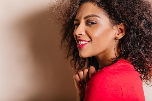 魅力的な若い女性のクローズアップの肖像画はイヤリングを着ています 無料写真