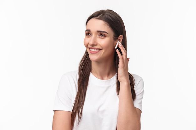 電話で話している魅力的な笑顔の若いブルネットの女性のクローズアップの肖像画 無料写真