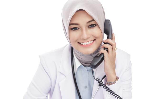 電話で話している美しいアジアの女性医師の肖像画を閉じる Premium写真