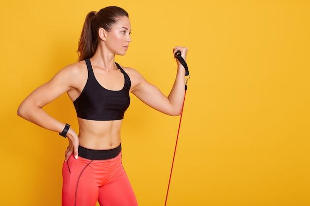 Конец вверх по портрету красивой атлетической девушки выполняет тренировки используя диапазон сопротивления, молодой. сила, мотивация и фитнес-концепция. Бесплатные Фотографии