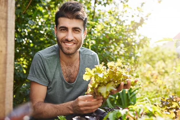 Крупным планом портрет красивого темнокожего бородатого кавказского фермера, улыбающегося, работающего в саду, собирающего листья салата, готовящегося к вечерней встрече с друзьями в своем доме Бесплатные Фотографии