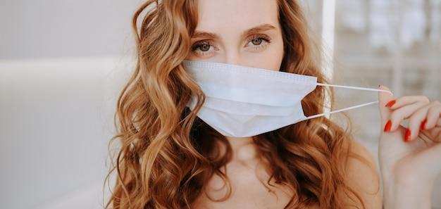Закройте вверх по портрету красивой молодой европейской женщины нося защитную маску для предотвращения вируса короны, гигиены для того чтобы остановить распространение коронавируса. избегайте заражения вирусом короны концепция covid-19 Premium Фотографии