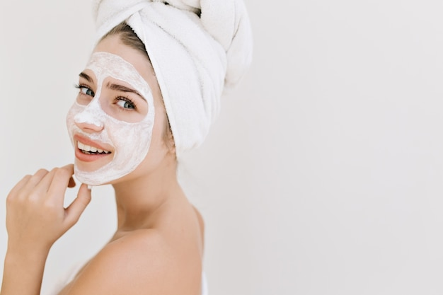 걸릴 목욕 후 수건으로 아름 다운 젊은 여자의 클로즈업 초상화는 그녀의 얼굴에 화장품 마스크를 확인합니다. 무료 사진