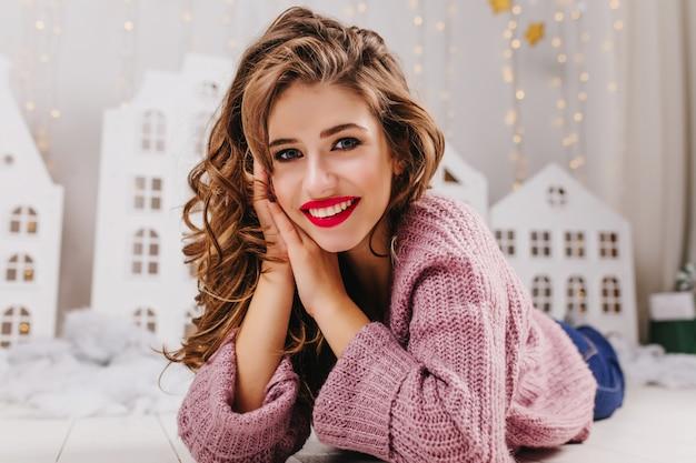 おもちゃの家と居心地の良い冬の雰囲気の中で床に横たわっている間微笑んで、赤い口紅と青い目の巻き毛の女の子のクローズアップの肖像画。 無料写真