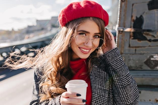 Портрет крупным планом голубоглазой белой женщины с искренней улыбкой, позирующей на городском фоне утром Бесплатные Фотографии