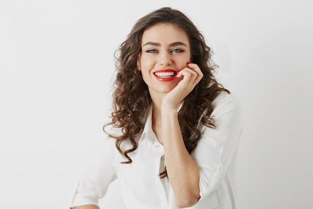 Крупным планом портрет откровенной улыбающейся привлекательной женщины с изолированными белыми зубами, длинные вьющиеся волосы, белая блузка, элегантный деловой стиль, счастливые положительные эмоции, красная помада макияж Бесплатные Фотографии