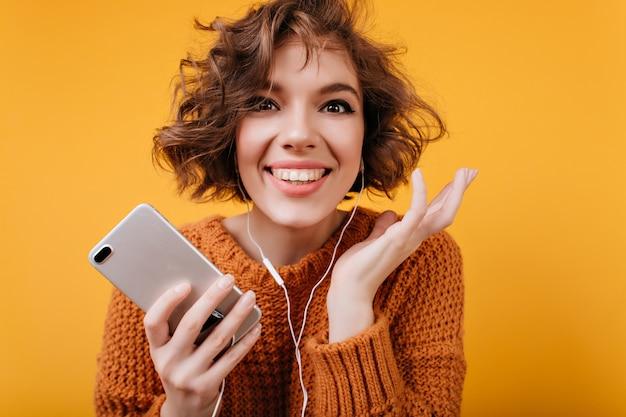 Крупным планом портрет веселой женской модели, наслаждающейся любимой музыкой во время фотосессии Бесплатные Фотографии