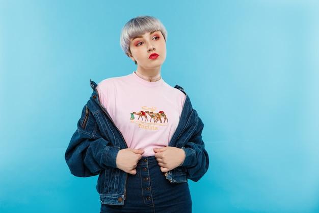 Крупным планом портрет уверенно красивая кукольная девушка с короткими светло-фиолетовыми волосами в повседневной уличной джинсовой куртке над синей стеной Бесплатные Фотографии
