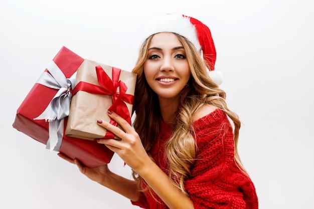 빛나는 물결 모양의 금발 머리 선물 상자와 함께 포즈와 귀여운 평온한 여자의 초상화를 닫습니다. 빨간 산타 가장 무도회 모자와 스웨터를 입고. 무료 사진