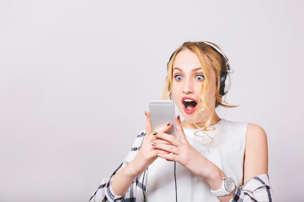 Крупным планом портрет милой экстатической рад женщины, читающей что-то захватывающее в своем смартфоне. эмоциональная блондинка с широко открытыми голубыми глазами в белой стильной блузке. изолированный. Бесплатные Фотографии