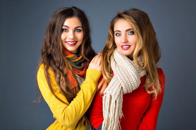 かなりかわいいブロンドとブルネットのかわいい女の子、抱擁、姉妹家族のスタイル、秋冬シーズン、セーターとスカーフを着ての肖像画を間近します。 無料写真
