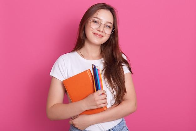 Крупным планом портрет милой молодой женщины, держащей учебник и цветные карандаши, позирует в студии, изолированных на розовый Бесплатные Фотографии