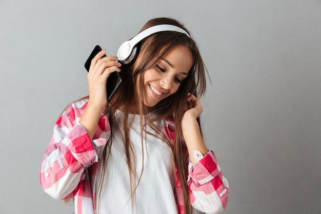 Портрет конца-вверх танцев музыки молодой счастливой женщины слушая с белыми наушниками Бесплатные Фотографии