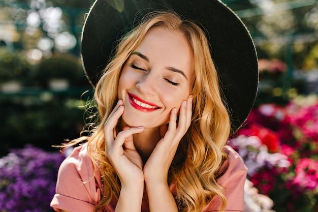 赤い唇を持つ恍惚とした盲目の女性のクローズアップの肖像画は黒い帽子をかぶっています。花の近くで目を閉じてポーズをとるdebinair白人女性。 無料写真