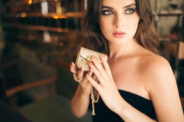 黒のベルベットのドレス、イブニングドレス、リッチでスタイリッシュな女性、エレガントなファッショントレンド、手に金色の財布を持ってヴィンテージカフェに座っているエレガントな美しい女性の肖像画をクローズアップ 無料写真