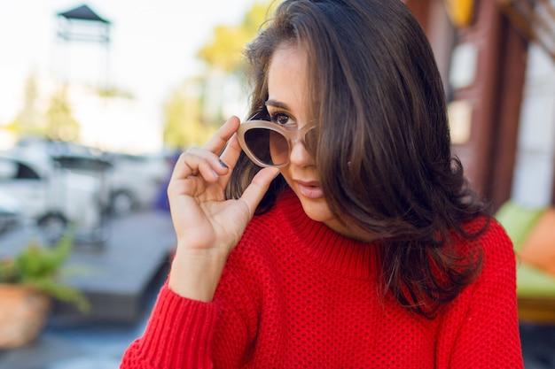 Крупным планом портрет элегантной романтической женщины с брюнетка волнистые волосы с стильные ретро очки и жених вязаный свитер. девушки отдыхают в современном кафе по утрам и пьют кофе. Бесплатные Фотографии