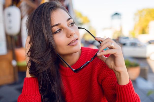 スタイリッシュなレトロなサングラスと水ニットのセーターでブルネットのウェーブのかかった髪を持つエレガントなロマンチックな女性の肖像画を閉じます。朝はモダンなカフェで身も凍るよう女性とコーヒーを飲みます。 無料写真