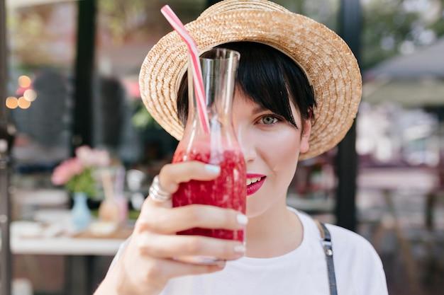 氷のレモネードのガラスを保持している黒い短い髪と薄い肌を持つエレガントな若い女性のクローズアップの肖像画 無料写真